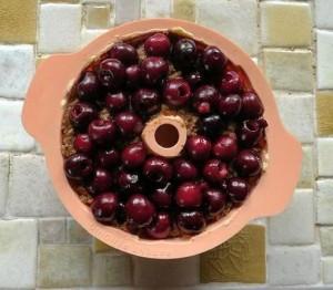 Backform mit Teig und aufgelegten Kirschen
